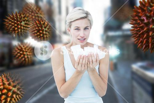 Composite image of sick woman holding tissues looking at camera