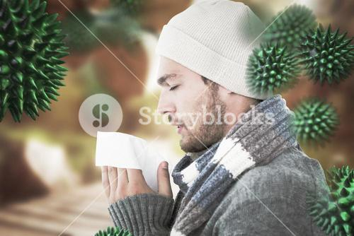 Composite image of handsome man in winter fashion blowing his nose