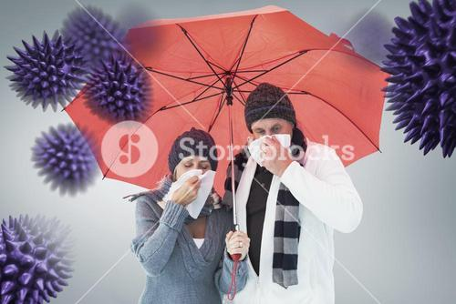 Composite image of mature couple blowing their noses under umbrella