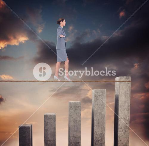 Composite image of businesswoman walking tightrope