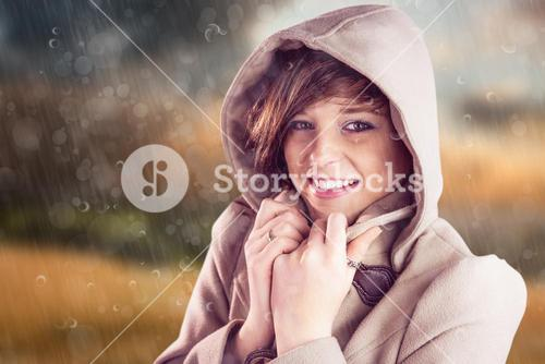 Composite image of portrait of smiling woman wearing winter coat