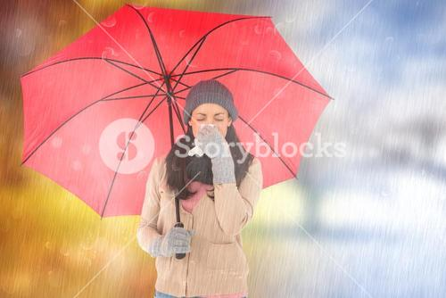 Composite image of sick brunette blowing her nose while holding an umbrella