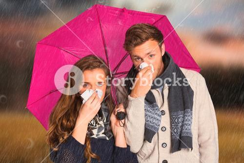 Composite image of couple blowing nose while holding umbrella