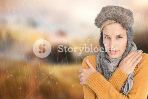 Composite image of woman in winter clothes shivering over white background