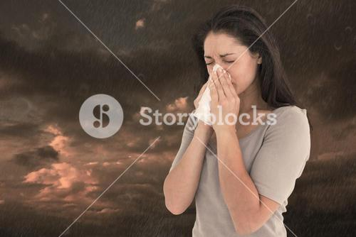 Composite image of sick brunette blowing her nose