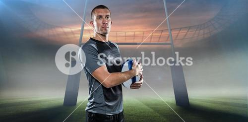 Composite image of confident rugby player in holding ball