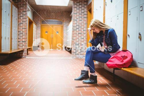 Worried student sitting with hand on head