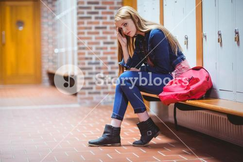 Worried student sitting in locker room and looking at the camera