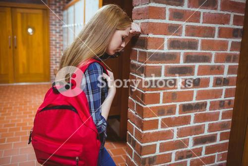Worried student leaning against the wall