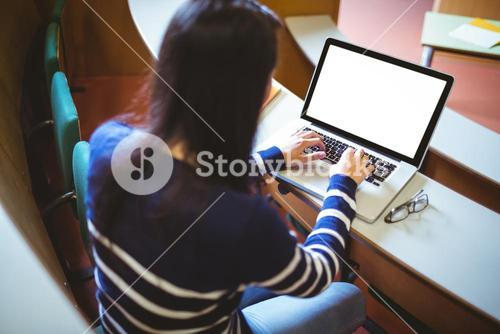 Happy student in lecture hall using laptop