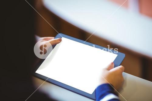 Student in lecture hall using tablet