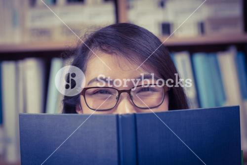Pretty student hiding face behind a book