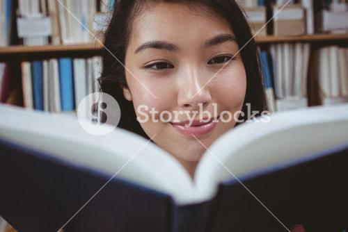 Smiling student reading a book