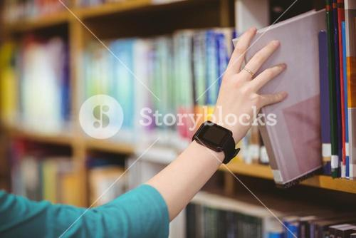 Students hand with smartwatch picking book from bookshelf
