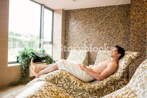 Handsome man relaxing in thermal suite