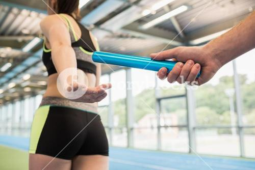 Man passing the baton to partner on track
