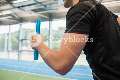 Fit man running on track with baton