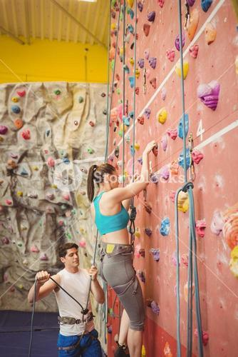 Instructor guiding woman on rock climbing wall