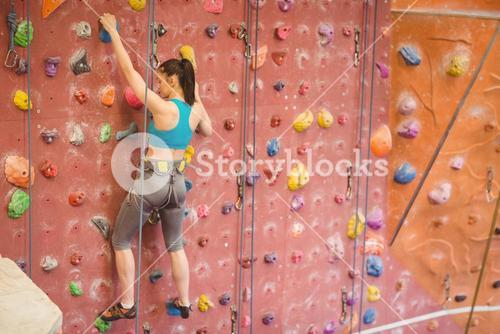 Woman climbing up rock wall