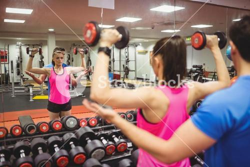 Fit couple working out in weights room