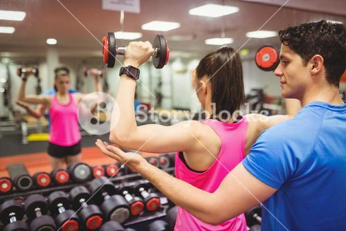 Woman lifting dumbbells with her trainer