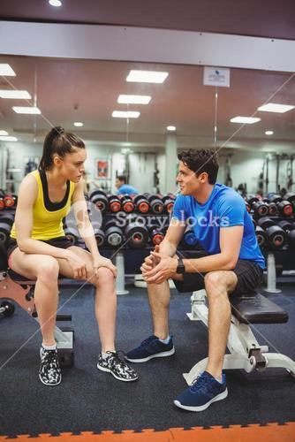 Fit couple chatting in weights room