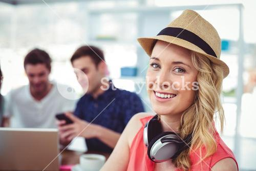 Smiling creative businesswoman working with co-workers
