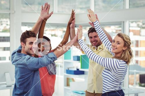 Happy creative team giving high fives to each other