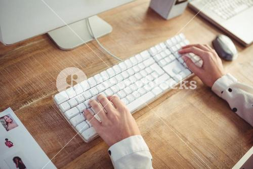 Cropped image of woman typing on keyboard