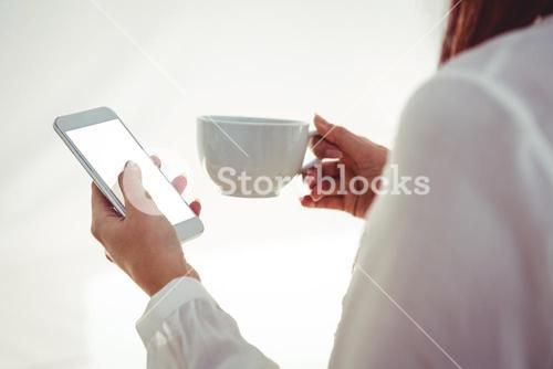 Woman with red hair using smartphone and holding coffee cup