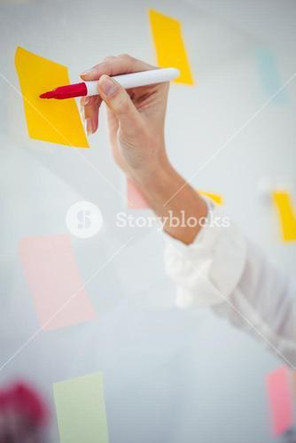 View of cropped hand writing on sticky note