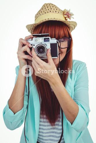 Portrait of a smiling hipster woman holding retro camera