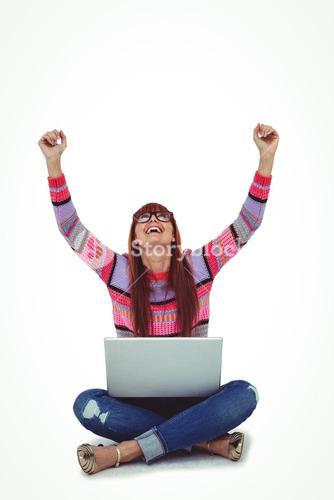 Smiling hipster woman using laptop while putting hands up