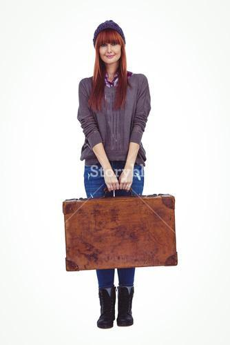 Smiling hipster woman holding suitcase
