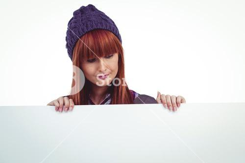 Smiling hipster woman holding big white card