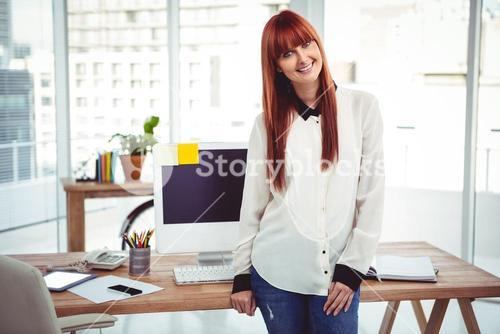 Smiling hipster businesswoman front of her desk