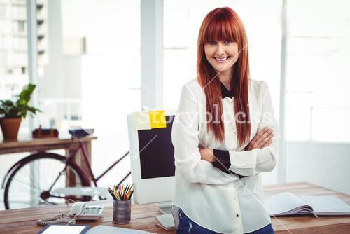 Smiling hipster businesswoman with arms crossed
