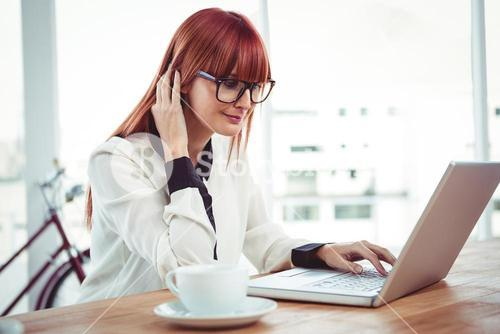 Smiling hipster businesswoman using her laptop