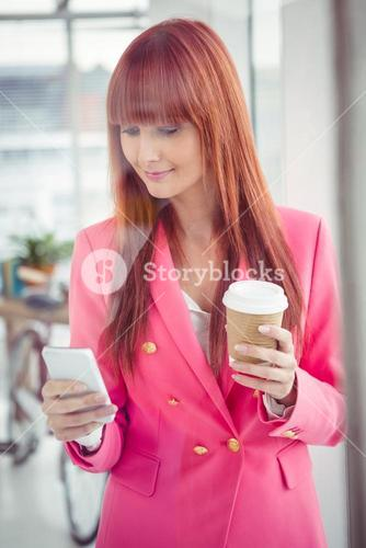 Hipster businesswoman holding coffee cup and smartphone