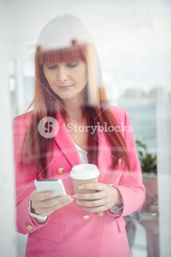 Hipster businesswoman texting with her smartphone
