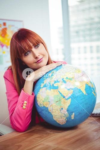 Hipster businesswoman lean on a globe