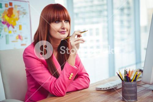 Hipster thoughtful businesswoman at her desk