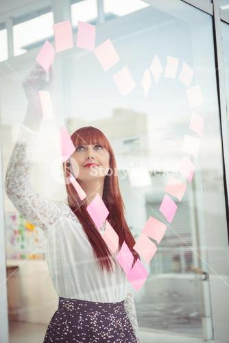Smiling hipster woman doing a heart in post-it