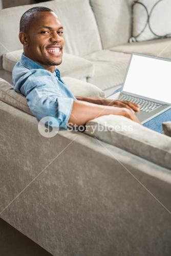Over shoulder view of casual man using laptop