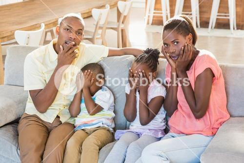 Portrait of a family of four watching tv