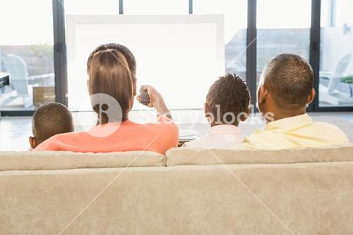 Over shoulder view of casual family watching tv