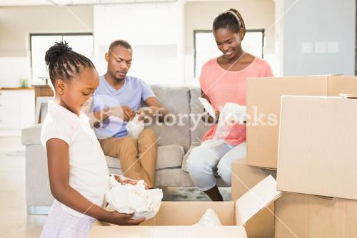 Family unwrapping things in new home