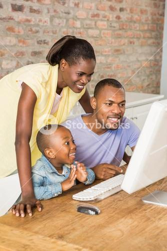 Casual smiling family on a computer