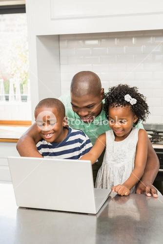 Father using laptop with his children in kitchen