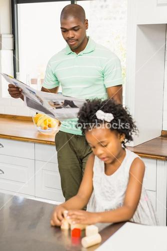 Concentrated father reading newspaper